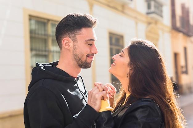 Jeune mec positif et heureuse dame tenant par la main sur la rue