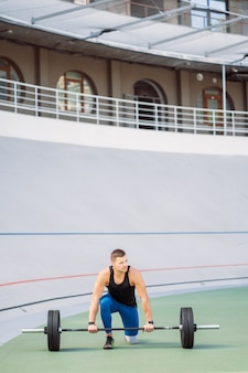Jeune mec soulève la barre dans le stade, séance d'entraînement en plein air