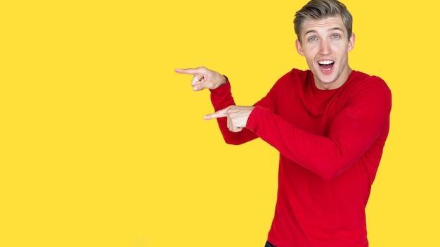 Jeune mec souriant d'apparence européenne sur fond jaune. dirige deux doigts de la main vers un espace vide