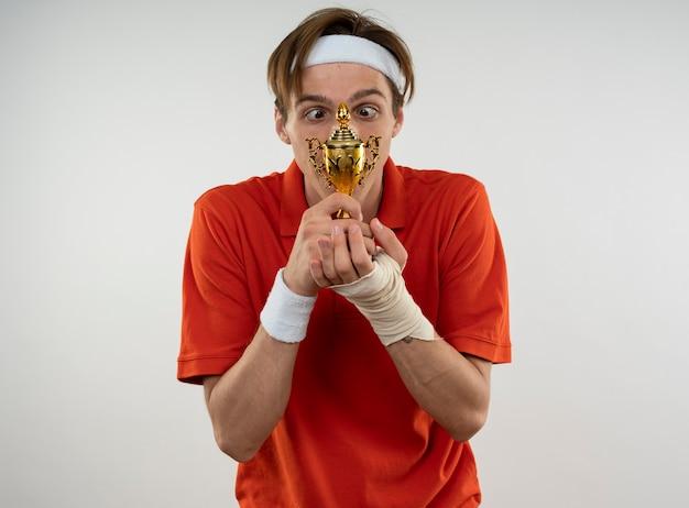 Jeune mec sportif portant bandeau avec bracelet avec poignet enveloppé de bandage tenant et regardant la coupe gagnant isolé sur mur blanc
