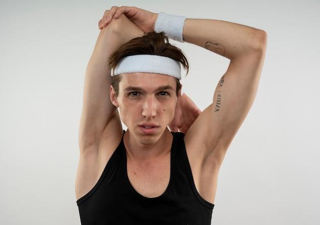 Jeune mec sportif portant bandeau et bracelet tenant les mains derrière le cou isolé sur mur blanc
