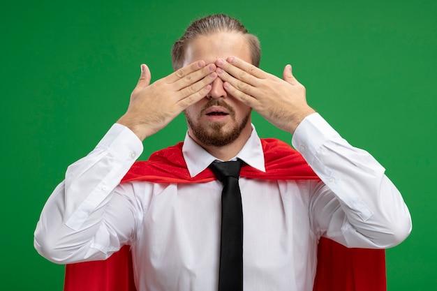 Jeune mec de super-héros couvert les yeux avec les mains isolées sur le vert