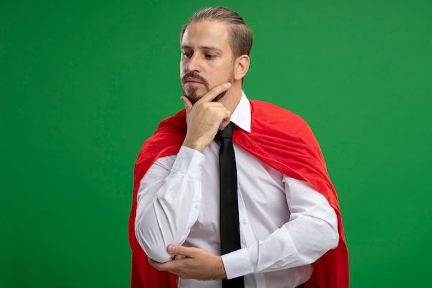 Jeune mec de super-héros mettant la main sur le menton isolé sur vert