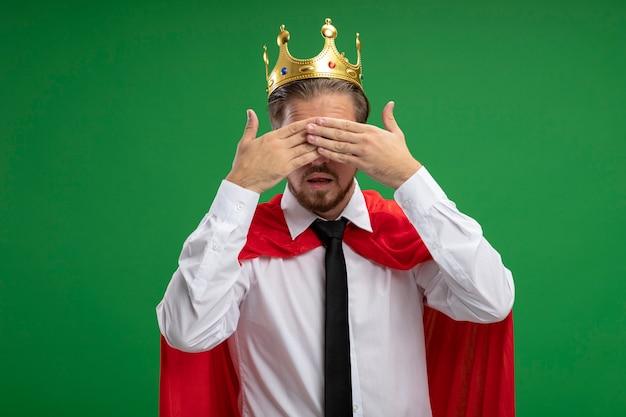 Jeune mec de super-héros portant couronne et cravate couverts yeux avec mains isolés sur vert