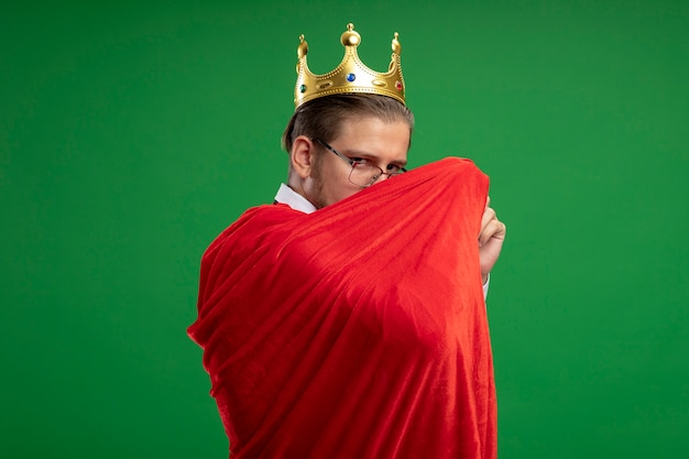 Jeune mec de super-héros portant couronne et cravate enveloppé dans un manteau isolé sur vert