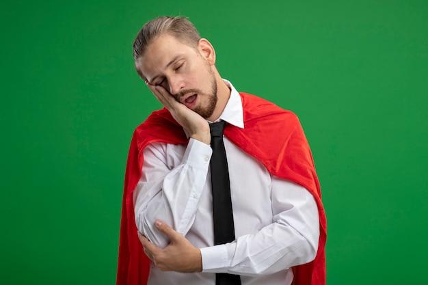 Jeune mec de super-héros portant une cravate avec les yeux fermés montrant le geste de sommeil isolé sur vert
