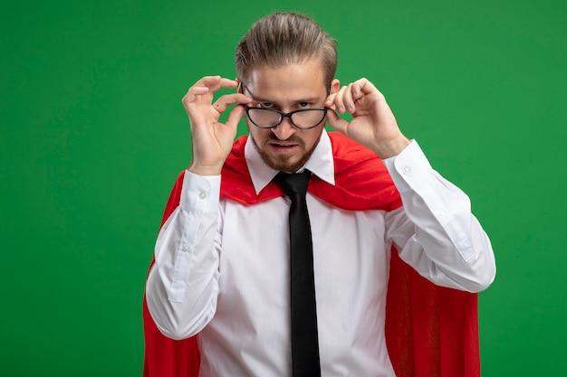 Jeune mec de super-héros strict portant une cravate et a attrapé des lunettes sur les yeux isolés sur vert