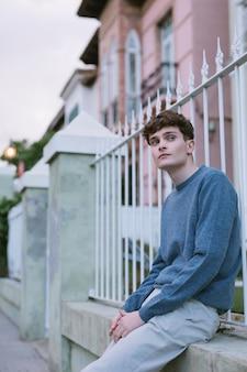 Jeune mec en tenue décontractée assis près des bâtiments