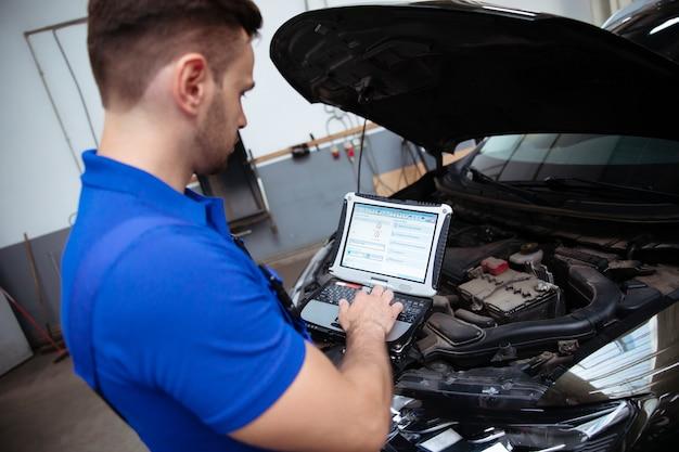 Jeune mécanicien automobile confiant et beau avec un ordinateur portable à la main effectue des diagnostics informatiques pour les erreurs dans les systèmes de la voiture