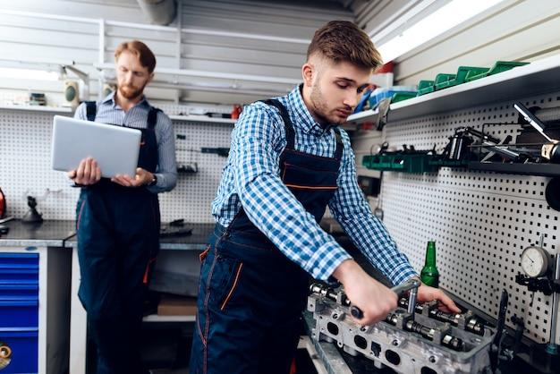 Jeune mécanicien automobile, détail des réparations dans le garage.
