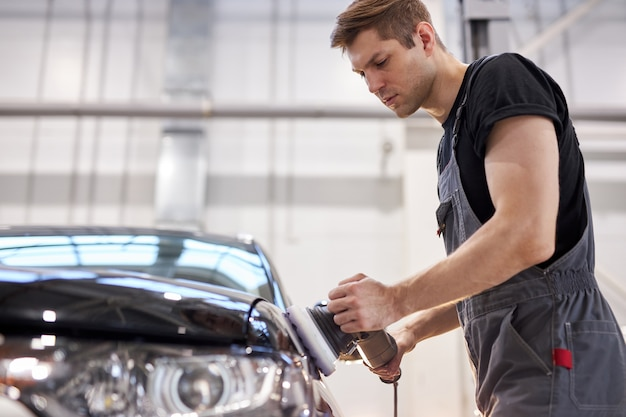 Jeune mécanicien automobile professionnel caucasien est la machine de polissage