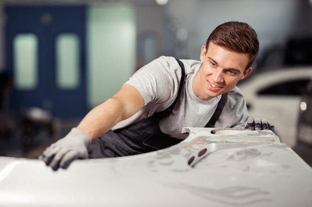 Un jeune mécanicien automobile qualifié répare une voiture dans un service de voitures et de véhicules.