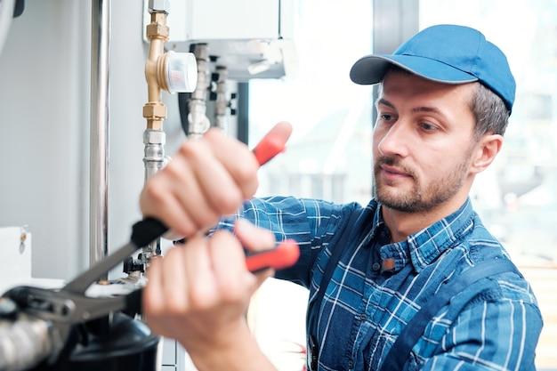 Jeune mécanicien contemporain du service d'entretien ménager réparant des tuyaux dans la cuisine du client