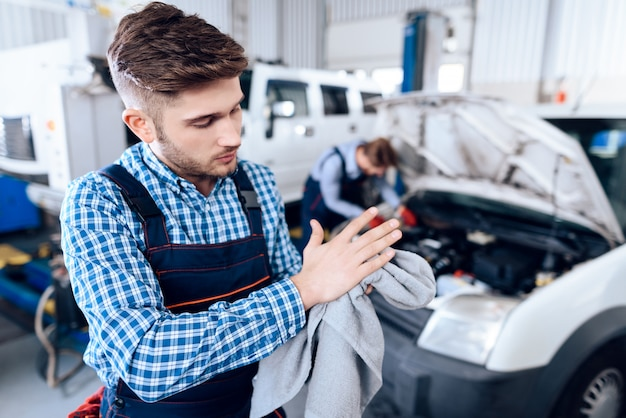 Jeune mécanicien essuie les mains avec une serviette dans un garage.