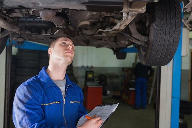 Jeune mécanicien sous l'écriture de voiture dans le presse-papiers en atelier