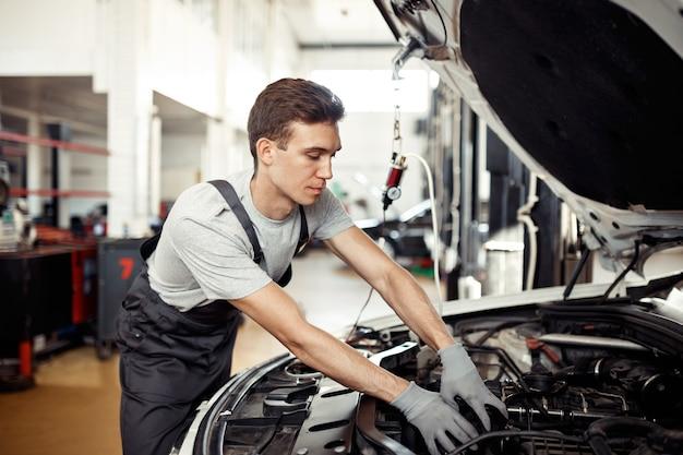 Un jeune mécanicien sympathique répare un véhicule à son travail.