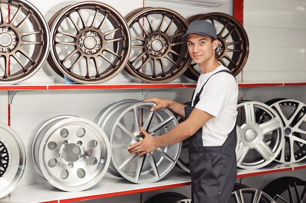 Un jeune mécanicien en uniforme se tient près de plusieurs jantes de pneus.