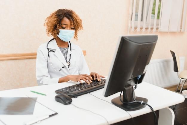 Jeune médecin africain attrayant avec masque facial