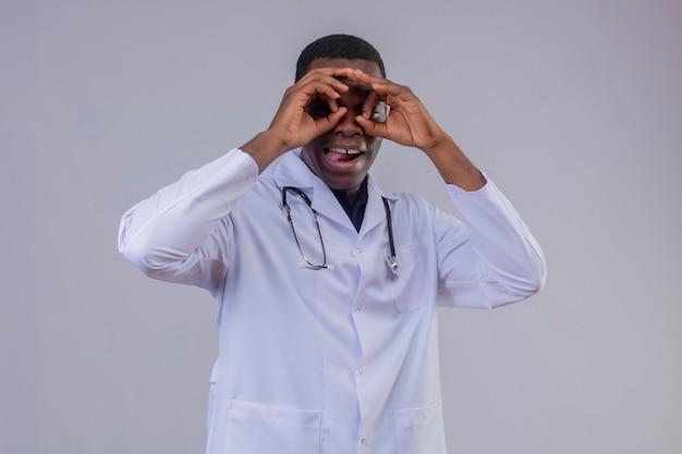 Jeune médecin afro-américain portant blouse blanche avec stéthoscope faisant le geste ok comme des jumelles à la recherche à travers les doigts qui sort la langue