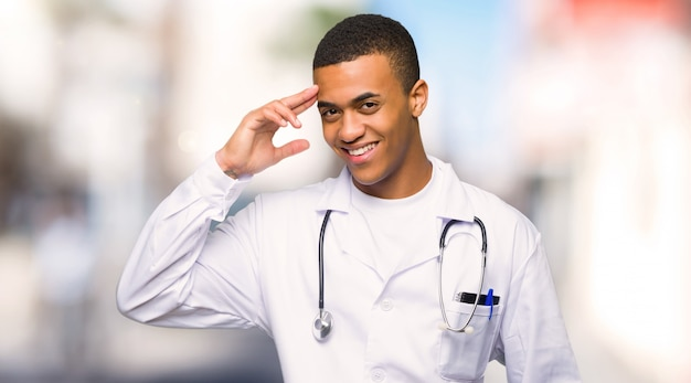 Jeune médecin afro américain saluant avec la main à l'extérieur