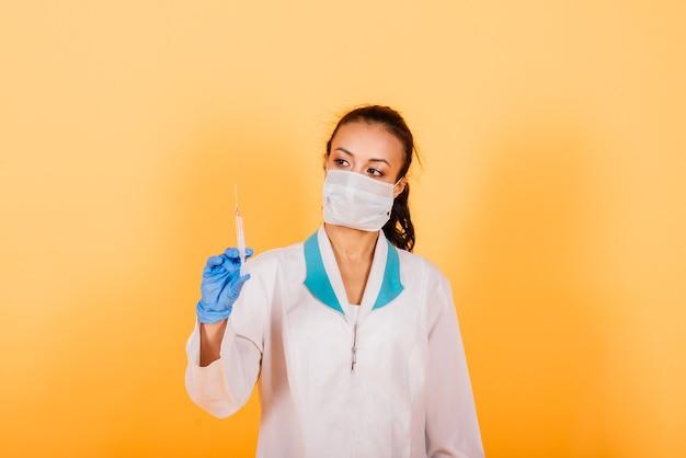Jeune médecin afro-américain souriant en masque médical tenant une seringue