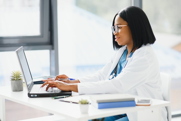 Jeune médecin afro-américain travaillant sur ordinateur portable en clinique