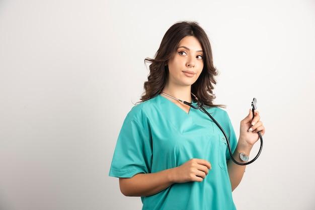 Jeune médecin à l'aide d'un stéthoscope sur blanc.