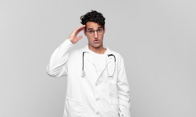 Jeune médecin à l'air heureux, étonné et surpris, souriant et réalisant une bonne nouvelle incroyable et incroyable