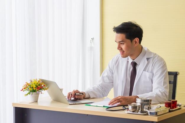 Un jeune médecin asiatique sourit et travaille sur le bureau de l'hôpital.