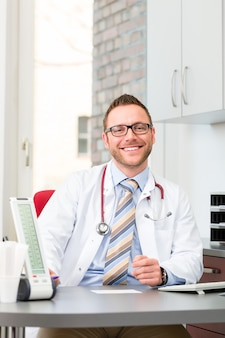 Jeune médecin assis en chirurgie au bureau