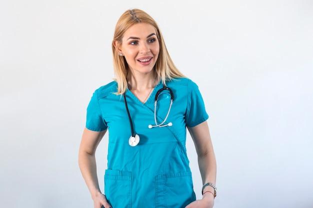 Jeune médecin blonde travaillant à l'hôpital, concept de soins de santé et médical stéthoscope autour du cou. femme médecin debout tout droit sur fond blanc