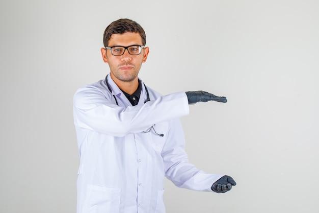 Jeune médecin en blouse blanche avec stéthoscope montrant un signe de grande taille avec les mains