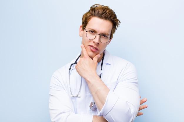 Jeune médecin chef à la recherche de sérieux, pensif et méfiant, bras croisés et main sur le menton, options de pondération sur le mur bleu