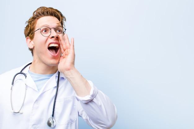 Jeune médecin chef rouge criant fort et en colère de copier l'espace sur le côté, avec la main à côté de la bouche contre le mur bleu