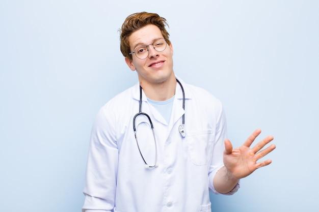 Jeune médecin chef rouge souriant joyeusement et joyeusement, agitant la main, vous souhaitant la bienvenue et vous saluant, ou disant au revoir mur bleu
