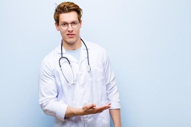 Jeune médecin chef rouge souriant joyeusement, se sentant heureux et montrant un concept dans l'espace de la copie avec la paume de la main