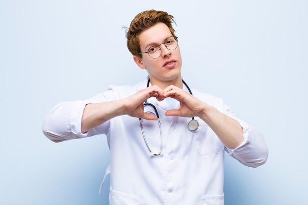 Jeune médecin chef souriant et se sentant heureux, mignon, romantique et amoureux, mettant en forme de coeur avec les deux mains contre le mur bleu