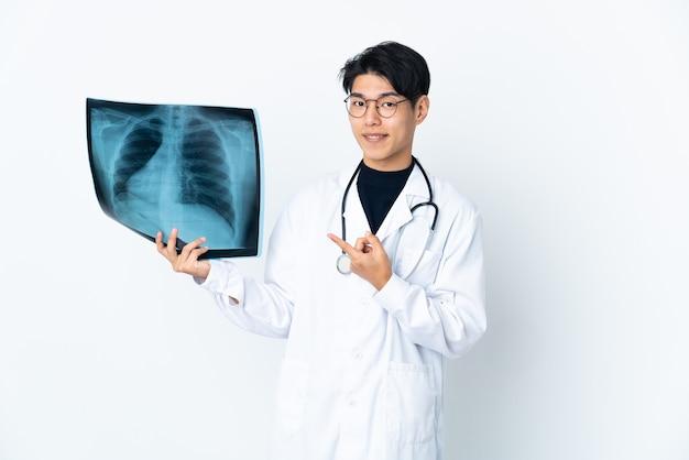 Jeune médecin chinois man holding radiographie isolé sur un espace blanc doigt pointé sur le côté