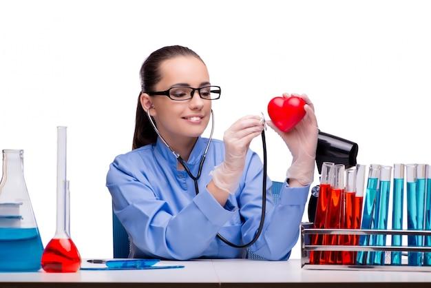 Jeune médecin avec coeur rouge isolé sur blanc