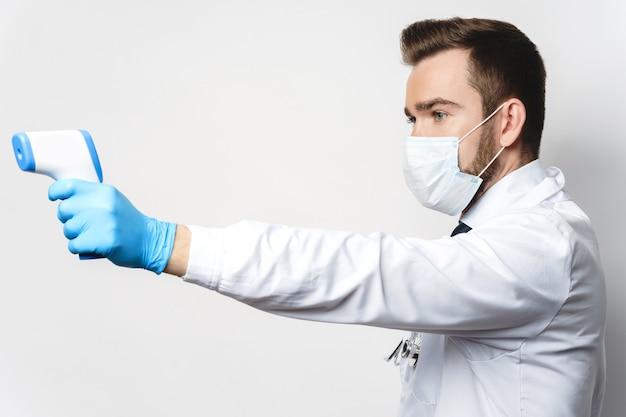 Un jeune médecin confiant mesure la température corporelle avec un thermomètre infrarouge