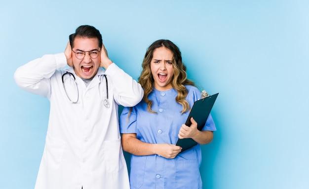 Jeune médecin couple posant dans un mur bleu isolé couvrant les oreilles avec les mains en essayant de ne pas entendre un son trop fort.