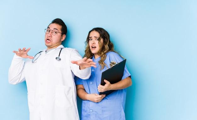 Jeune médecin couple posant dans un mur bleu isolé étant choqué en raison d'un danger imminent