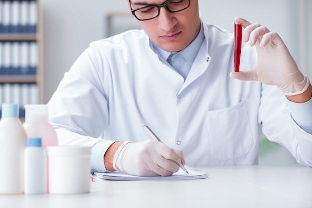 Jeune médecin dans le laboratoire avec tube rouge