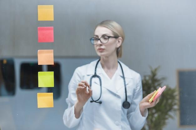 Un jeune médecin élabore un plan stratégique, colle des autocollants colorés sur un verre transparent.