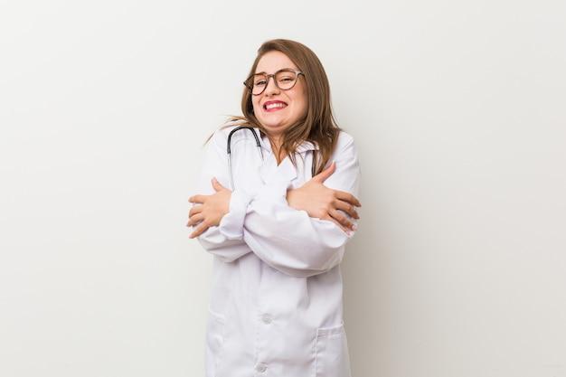 Jeune médecin femme contre un mur blanc qui devient froide en raison d'une température basse ou d'une maladie