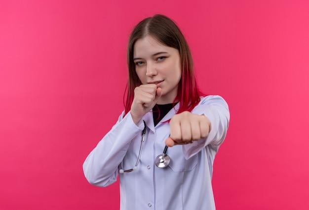 Jeune médecin femme portant une robe médicale stéthoscope debout dans la lutte contre la pose sur le mur isolé rose