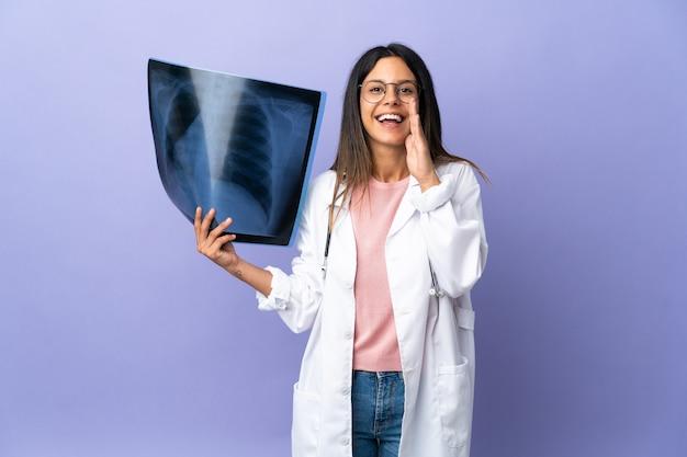 Jeune médecin femme tenant une radiographie criant avec la bouche grande ouverte