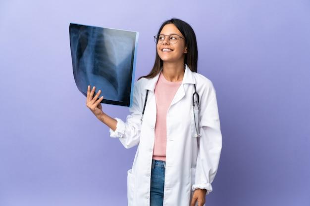 Jeune médecin femme tenant une radiographie en pensant à une idée tout en levant