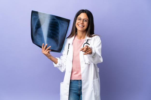 Jeune médecin femme tenant une radiographie pointant vers l'avant avec une expression heureuse