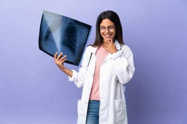 Jeune médecin femme tenant une radiographie à la recherche sur le côté et souriant